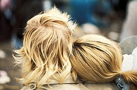 close up back view of a a blond couple with the girl's head on the boy's shoulder