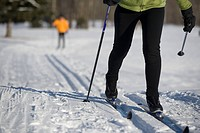 Couple cross_country skiing on groomed ski trails.