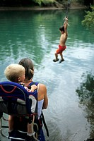 Mother and son watch boy jump in water.