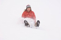A woman sledding during snowstorm.