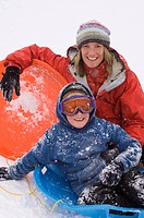 Mother and son sledding during snowstorm.