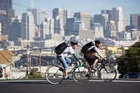 Two bike messengers ride in city.