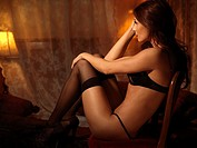 Glamour photo of a sexy young woman in lingerie sitting in a chair
