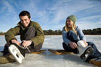 Young couple laces up their ice skates.