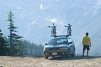 Man with mountain bikes on car.