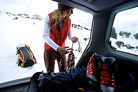 A woman preparing to go ice climbing and arranging gear from her trunk.