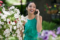 Young Woman in Garden With Cell Phone