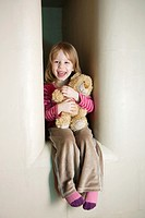 Three Year Old Girl Sitting in Stove Recess With Teddy Bear