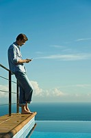 Man standing beside infinity pool, text messaging with cell phone