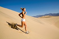A young woman running down a steep sand dune in Death Valley, California.