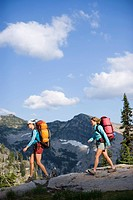 Two adult women backpacking in a wilderness area under a bright blue sky.