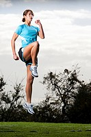 An athletic woman jumping in the air to prepare for a run in San Diego, California.