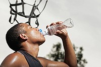 Young man drinks water after playing basketball at Barstow Park in Vermillion, South Dakota. lit with flash