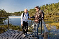 Young Couple Standing on Wooden Boardwalk in Meenikunno Bog by Water, Estonia