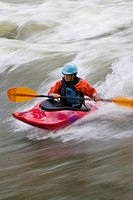 A young, Asian_looking woman surfing a wave in a whitewater kayak, Elk river, East Kootenies, British Columbia, Canada.