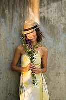 Smiling woman in yellow sundress holds bouquet