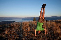 Young man doing a head stand at sunset in Idaho.