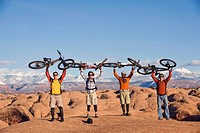 Four young men hold their bikes above their heads on the Slickrock Trail, Moab, UT.