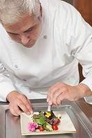 Mid_ adult chef arranges edible flowers on salad