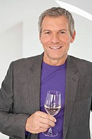 Germany, Munich, Mature man with wine glass, smiling, portrait