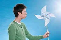 Teenage boy holding paper windmill