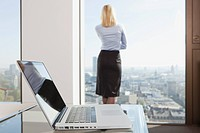 Germany, Frankfurt, Business woman looking through window with laptop in foreground