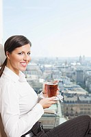 Germany, Frankfurt, Business woman drinking tea, smiling, portrait