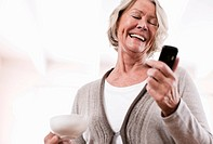 Germany, Wakendorf, Senior woman using mobile and smiling