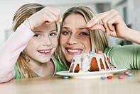 Germany, Cologne, Mother and daughter decorating cake, smiling, portrait
