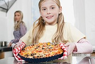 Germany, Cologne, Girl holding pizza with mother in background