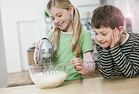 Germany, Cologne, Girl and boy mixing batter using electric whisk