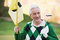 Italy, Kastelruth, Mature man holding golf club and golf flag, smiling