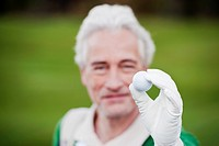 Italy, Kastelruth, Mature man holding golf ball, smiling, portrait