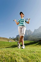 Italy, Kastelruth, Mid adult woman with golf club on golf course