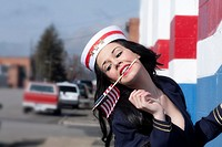 A young woman dressed as a sailor in a pin-up style, with an American flag