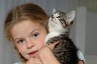 Germany, Bavaria, Girl holding her pet cat, portrait