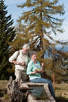 Italy, South Tyrol, Mature couple sitting at trough and having snacks
