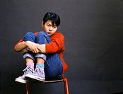 Studio image of a an Asian teenage girl sitting on a chair clasping her knees and looking forlorn