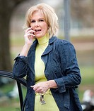 Fifty year old blond woman talking on a mobile phone, outdoors near a car