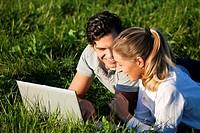 Paar auf Wiese mit WLAN im Internet