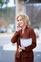 Fifty year old blond woman in business attire talking on a mobile phone