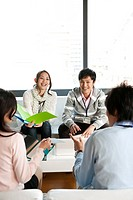 Businesspeople sitting on sofa and having a meeting, Tokyo Prefecture, Honshu, Japan