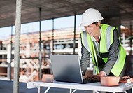 Construction worker using laptop on construction site (thumbnail)