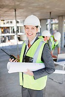 Construction worker holding walkie talkie and blueprints on construction site