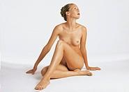 Nude woman looking sitting, upwards