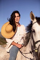 dark haired lady with strawhat doing horseback ridning on an Andalusian horse