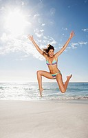 Excited woman in bikini jumping on beach