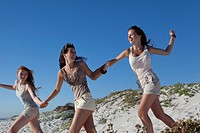 Three girls running down hill