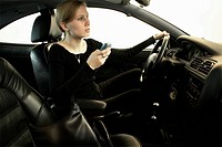 Woman in drivers seat writing a text message