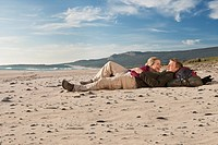 Young backpackers lying on beach